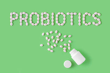 Probiotics word made of pills on green background. Flat lay, top view, free copy space.