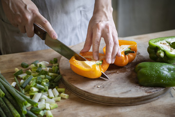 Cook slicing bell peppers on a cutting board