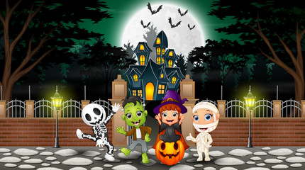 Happy kids wearing halloween costume outdoors with the haunted house background