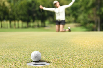 Woman golfer cheering after a golf ball on a golf green