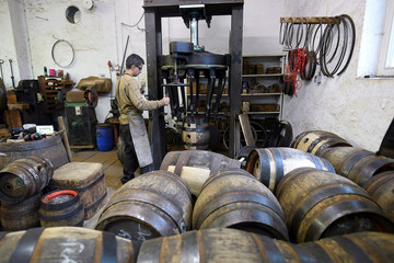 """An apprentice restores used beer barrels in the workshop of """"Fass Schmid"""", which builds beer barrels the traditional way, in Munich"""