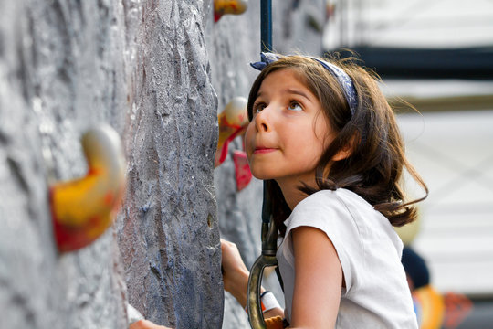 Young Girl About to Climb Rock Wall Looks Up With a Bit of Worry