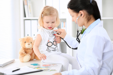 Doctor and patient baby in hospital. Little girl is being examined by pediatrician with stethoscope. Health care, insurance and help concept