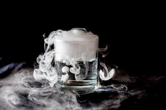 Glass with white smoke at dark background