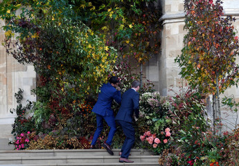 People try to fix foliage at St George's Chapel before the royal wedding of Princess Eugenie and Jack Brooksbank in Windsor Castle