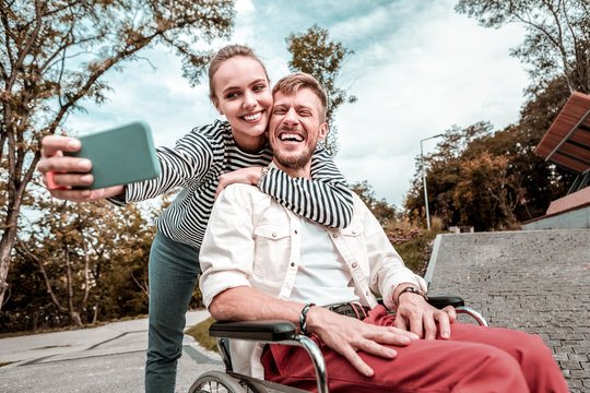 Funny selfie. Positive happy young man sitting in the wheelchair and laughing while loving woman taking selfies with him