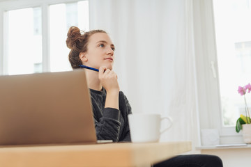 Thoughtful young woman working at a desk