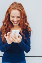Young smiling red-haired woman using mobile phone