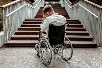 Many stairs. Horizontal image of depressed disabled man sitting in the wheelchair and facing the difficulties with climbing the stairs alone