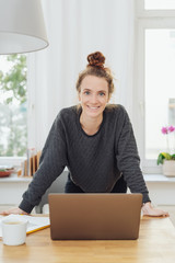 Woman smiling at camera while leaning on table