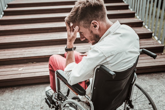 Oh no. Sad invalid young man touching his forehead and looking depressed while sitting in wheelchair in front of high stairs