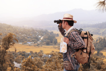 Young man with backpack and holding a binoculars and map paper is standing top of a mountain.