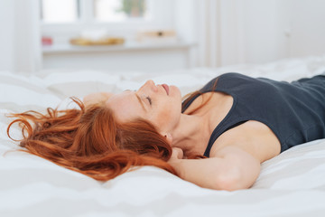Young red-haired woman taking nap on bed