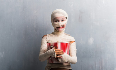 Boy in mummy costume eating popcorns for halloween holidays