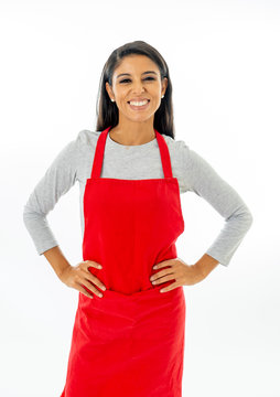 Portrait of a happy attractive woman wearing a red apron making thumb up gesture