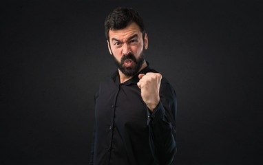 Angry man with beard on black background
