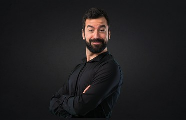 Handsome man with beard with his arms crossed on black background