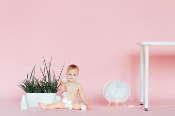 Nursery for children. Kids. Family morning at home. New born kid. Diaper. Child. Childhood. Kindergarten. Toys. Baby boy wearing diaper. Little boy