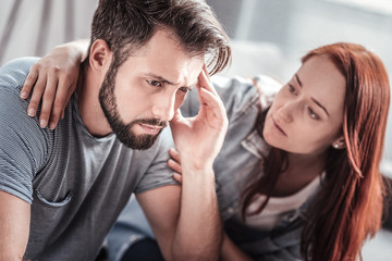 Period of depression. Depressed gloomy young man sitting together with his girlfriend and holding his forehead while thinking about their problems