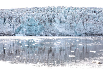 Isfjorden glacier front of blue ice in Svalbard on a summer day.