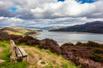 Wooden bench overlooking Mawddach river estuary at low tide with views to Snowdonia at low tide, near Barmouth, Wales