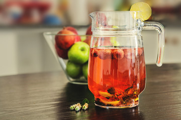 Pitcher and glass of fresh strawberry, mint and lemon slices water.