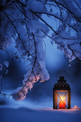 Candle lantern under the snowy branches at dusk. Christmas time in a wintery garden.