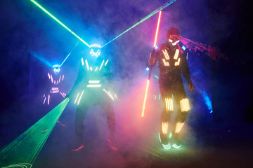 Laser show performance, dancers in led suits with LED lamp, very beautiful night club performance, party