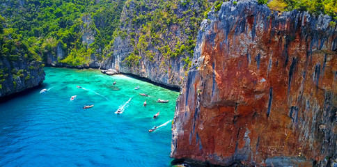 Multiple Boats in Loh Samah Bay, Thailand - Tropical Cove Surrounded by Lush Island Cliff Face With Turquoise Blue Water and Visible Coastal Reef - Aerial Overhead View