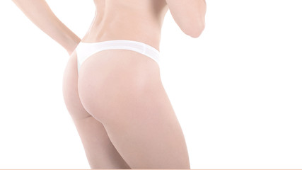 Female cropped buttocks in white thongs, isolated on white.