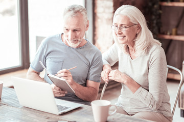 Curiosity. Portrait of attentive elderly couple sitting close to each other while looking at the laptop screen and making notes