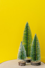 Christmas decoration three fir trees in front of a yellow background