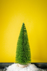 Christmas decoration a fir trees in front of a yellow background