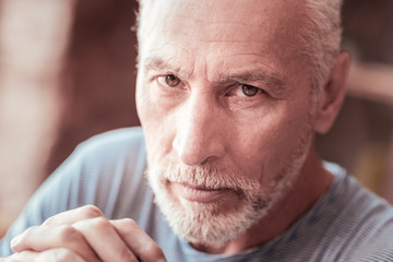 Shrewd glance. Close up of elderly man being serious while looking at you and expressing calmness
