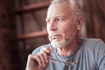 Positive thinking. Close up of elderly man keeping his glasses rim an his chin and looking away while being pleased