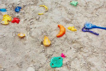 many colored plastic children's toys forgotten in the sandbox