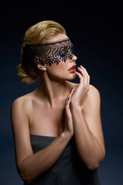 Creative portrait of a young woman in a lace mask.