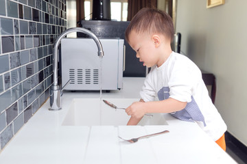 Cute little Asian 2 year old toddler boy child standing & having fun doing the dishes, concentrate on washing dishes in kitchen at home, Little home helper, chores for kids, child development concept