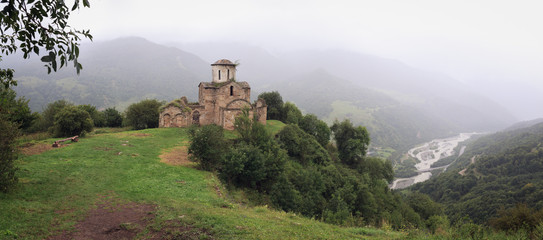 Fototapeta Panoramic view of an ancient monastery on top of a mountain in the Caucasus in Russia.