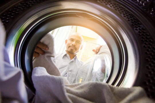 Bald man with mustache is bringing clothes or fabric in to the washing machine.