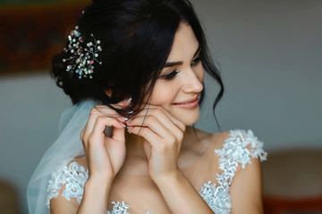 Wedding earrings on a female hand wear, she takes the earrings, the bride fees, morning bride, woman in white dress