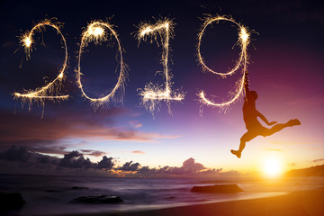 happy new year 2019. man jumping and drawing on beach