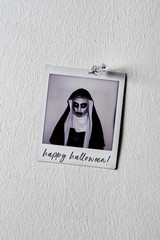 picture of an evil nun and text happy halloween
