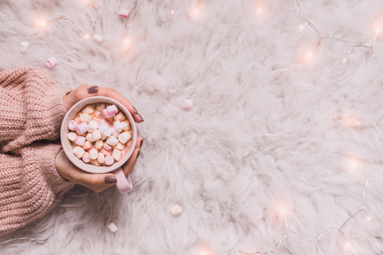 Cozy background. Hands holding mug of hot cocoa or hot chocolate with marshmallow on white rug.