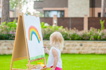 Cute baby girl boy drawing with colorful paints in summer park. Creative child painting on nature. Talented toddler painter