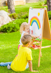 Children drawing with colorful paints in summer park. Creative child painting on nature. Talented toddler painter