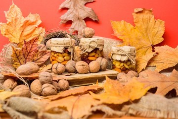 Storehouse of vitamins concept. Natural homemade treats autumn season keep healthy. Set three honey natural sweets in jars red background covered fallen leaves. Jars walnuts and fallen leaves