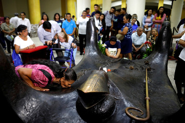 People pray at the grave of the late Archbishop of San Salvador, Mons. Oscar Arnulfo Romero at the Metropolitan Cathedral in San Salvador
