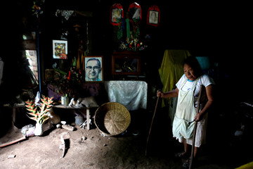 Crisitna Vasquez, head of the brotherhood of the Virgin of Belen stands by her altar with a picture of the late Archbishop of San Salvador, Mons. Oscar Arnulfo Romero in Izalco