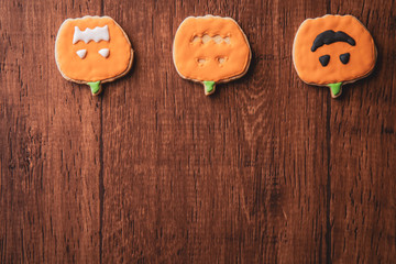 Fresh delicious homemade decorated halloween cookies sweets on dark wooden background, concept of halloween party, copy space(text space), top view, blank for text.